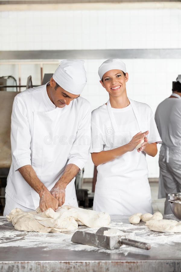 Female Baker Making Dough Balls By Male Colleague stock image