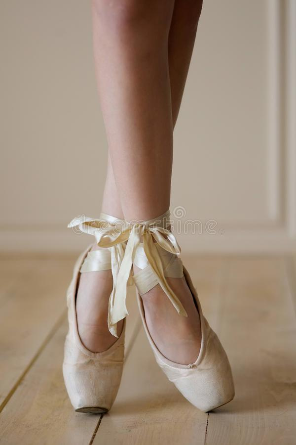 Female ballet dancer legs in white Pointe shoes stock images