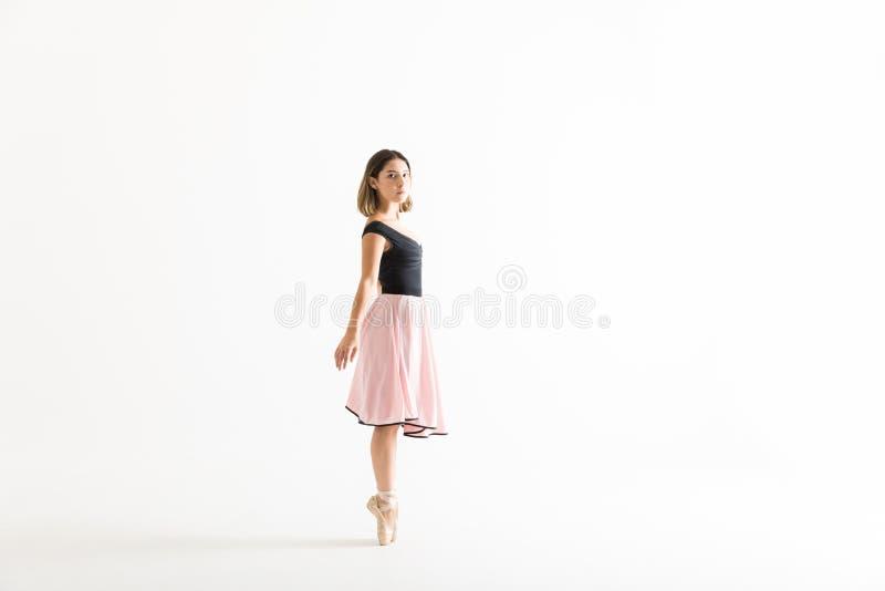 Female Ballet Dancer Maintaining Balance Over White Background stock photos