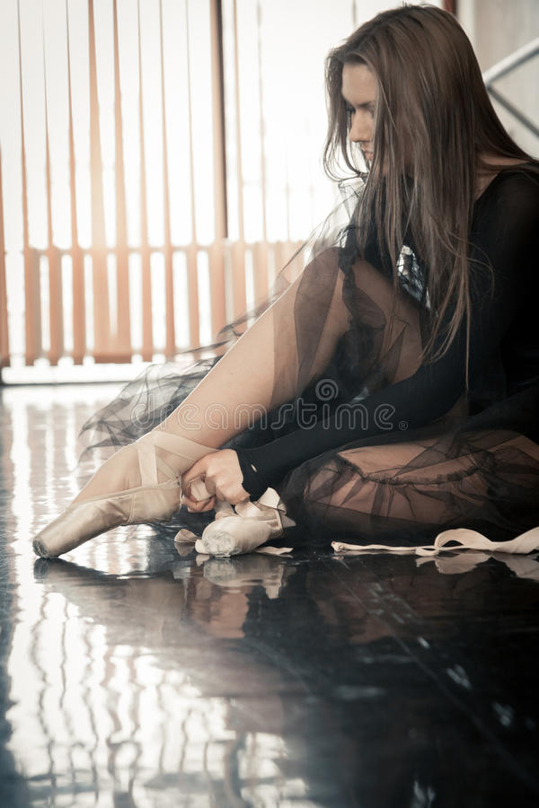 Female ballet dancer puts pointes on. Female ballet dancer sitting on a floor in a dancing class puttinf on her pointes royalty free stock photography