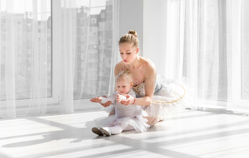 Female ballet dancer teaching little girl doing exarcises for stretching royalty free stock photo