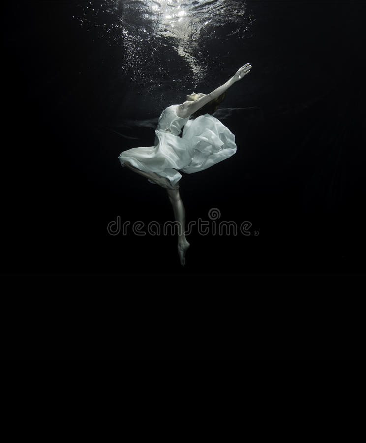 Ballerina underwater. A young female ballet dancers is dancing underwater royalty free stock images