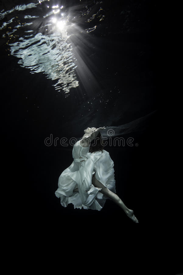 Ballerina underwater. A young female ballet dancers is dancing underwater royalty free stock photos
