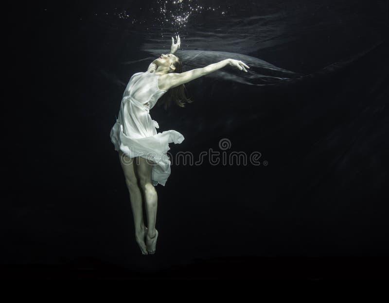 Bellerina underwater. A young female ballet dancers is dancing underwater stock photos
