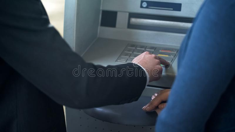 Female bank employee showing new client how to work with ATM, good service royalty free stock photos