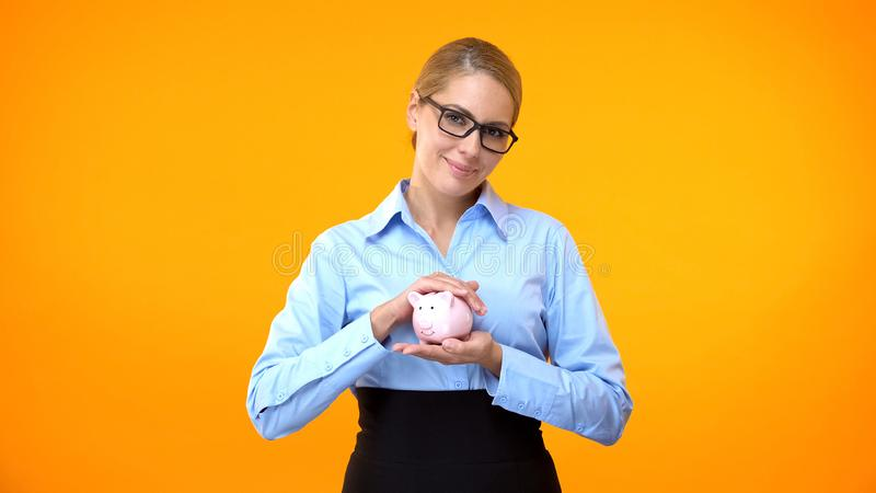 Female bank manager holding piggybank in hand, pension fund, deposit insurance stock images