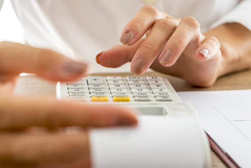 Female banker calculating expenses and income using adding machine royalty free stock photos