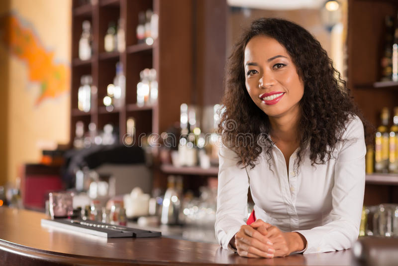 Female bar owner. Asian female bar owner standing behind counter and smiling at camera stock photography