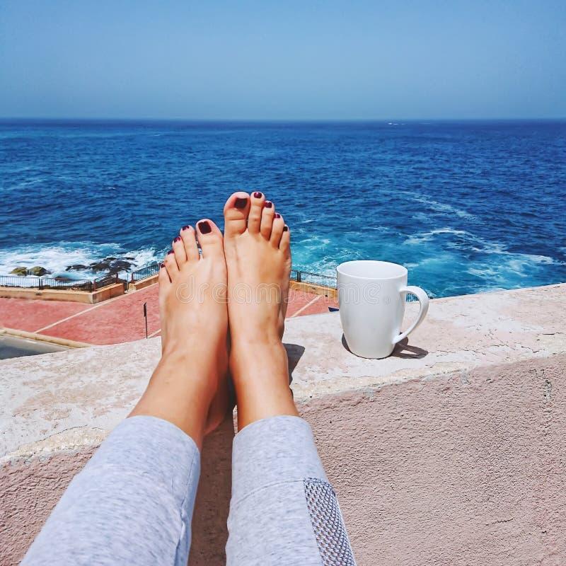 Female bare feet against blue sea and white mug of coffee stock photography