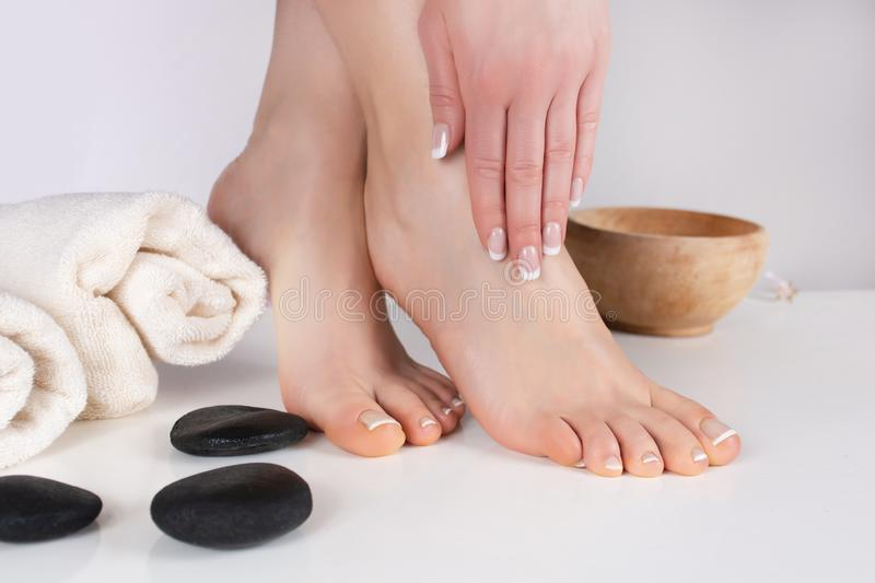 Female bare feet and hands with french manicure and pedicure in beauty salon with towel and decoration stone and wooden bowl. Young beautiful gently girl bare stock image