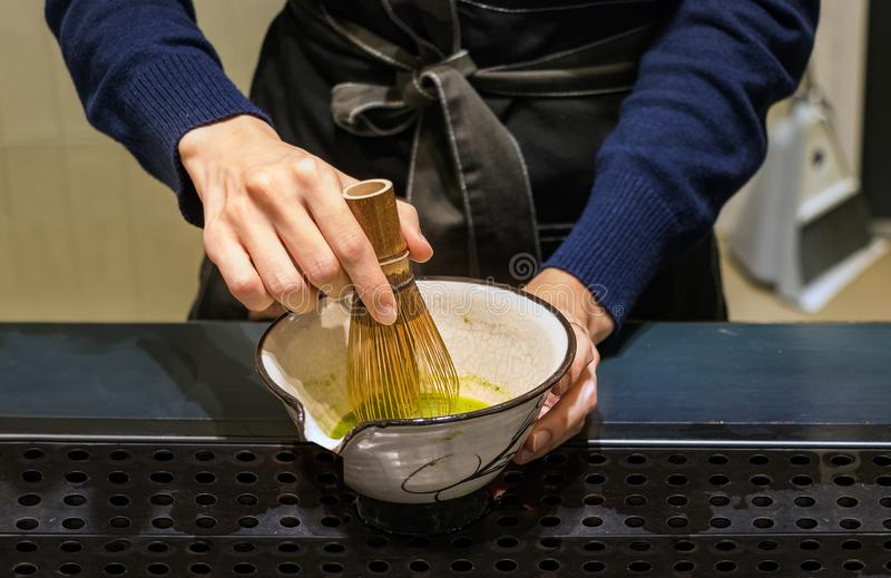 Female barista hands preparing matcha tea on a bowl, mixing it with a bamboo whisk in Busan, Korea royalty free stock photos