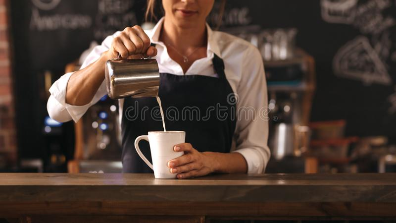 Female barista making a cup of coffee royalty free stock photos
