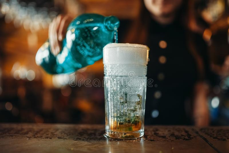 Female barman pours aerated water into a glass. Woman bartender mixing at the bar counter in pub. Barkeeper occupation stock photos
