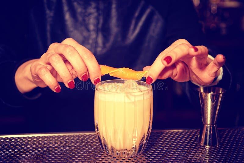 Female bartender is adding orange zest to cocktail, toned royalty free stock photo