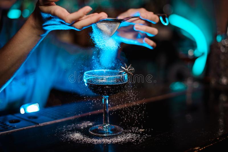 Female bartender adding to a cocktail decorated with badian a sugar powder through the strainer in the blue light royalty free stock image