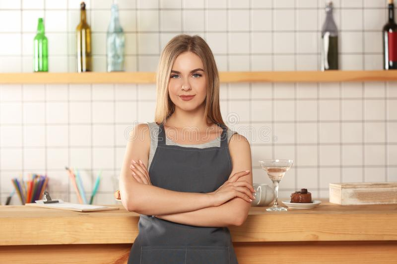 Female bartender with crossed arms in bar royalty free stock photo