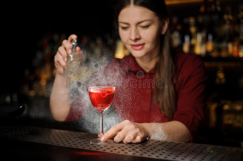 Female bartender decorating a glass of alcoholic cocktail with s royalty free stock image