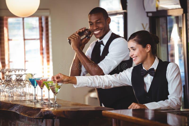 Female bartender garnishing cocktail with olive stock photo