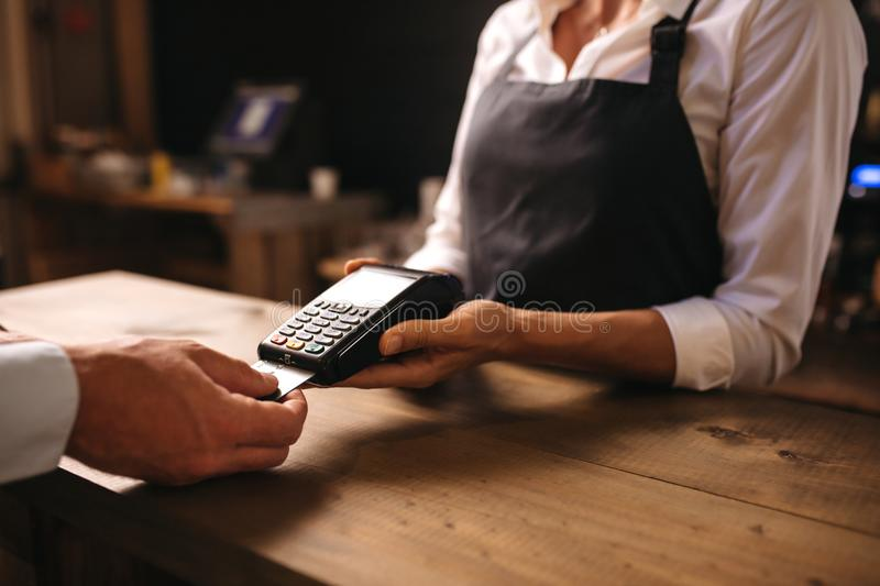 Man paying for coffee by credit card at coffee shop. Female bartender holding a credit card reader machine with male customer inserting the card in machine for royalty free stock image