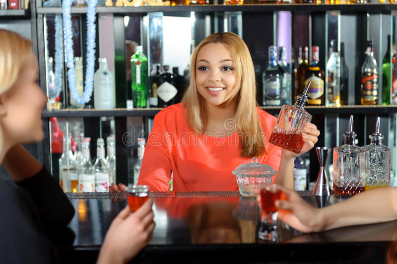 Female bartender makes cocktails. Talk at the bar. Smiling attractive female bartender talking to the guests holding a bottle with red drink stock photos