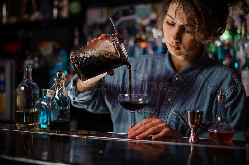 Female bartender pouring a brown alcoholic cocktail from the measuring cup to the glass royalty free stock photography