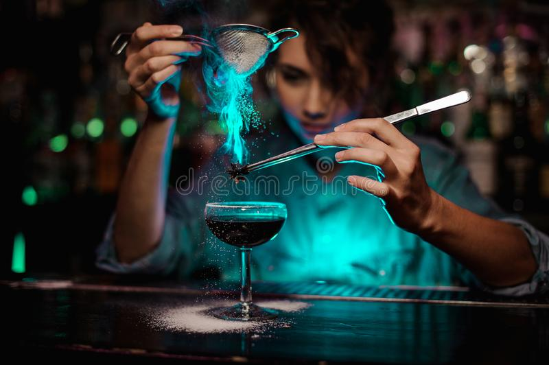 Female bartender pouring on the brown cocktail and on a flamed badian on tweezers a powdered sugar in the green light stock image