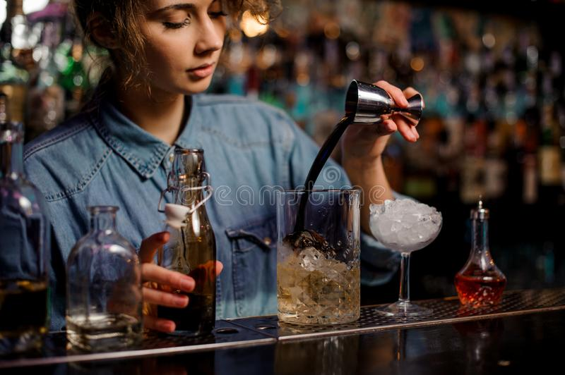 Female bartender pouring to the measuring glass cup with ice cubes a brown alcoholic drink from steel jigger royalty free stock image