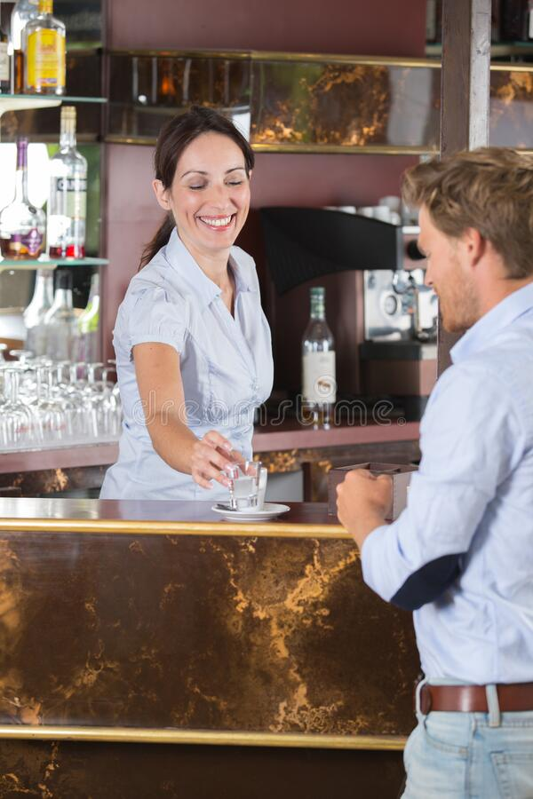 Female bartender serving drink to customer royalty free stock image