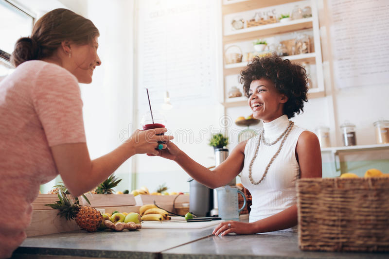 Female bartender serving a glass of fresh juice to customer royalty free stock photography