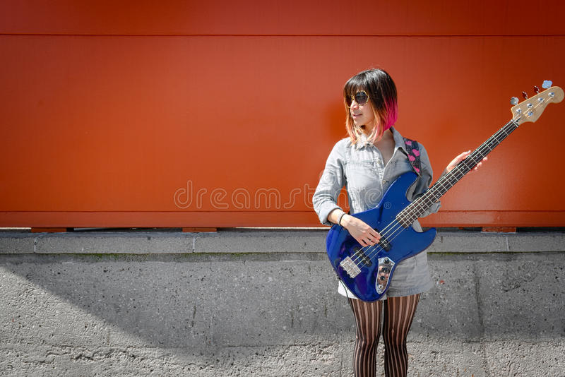 Female bass guitar player posing with blue bass. Three quarters portrait of young woman musician. Woman is posing with a blue bass guitar outdoors. Subject is royalty free stock image