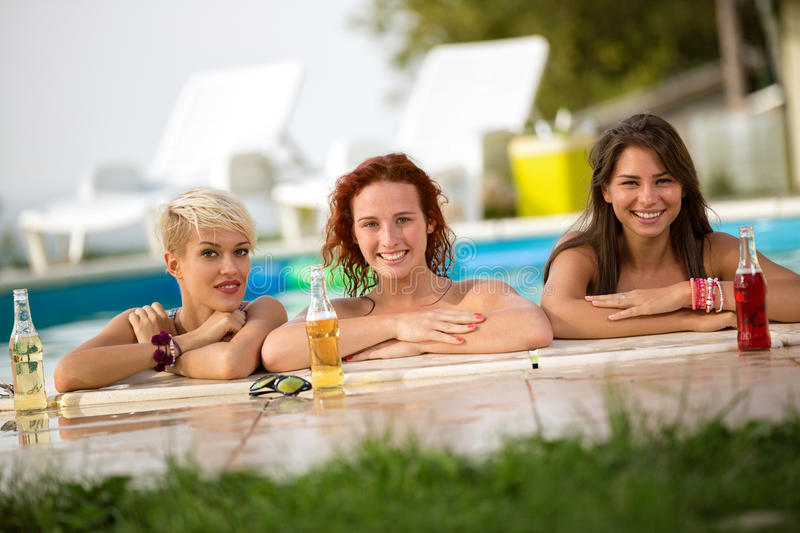 Female bathers standing in front of railing of pool with bottles. Three nice female bathers standing in front of railing of pool with bottles of refreshing royalty free stock image