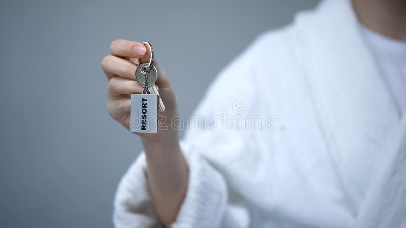 Female in bathrobe holding keys with Resort word, spa in hotel, all inclusive. Stock photo royalty free stock images