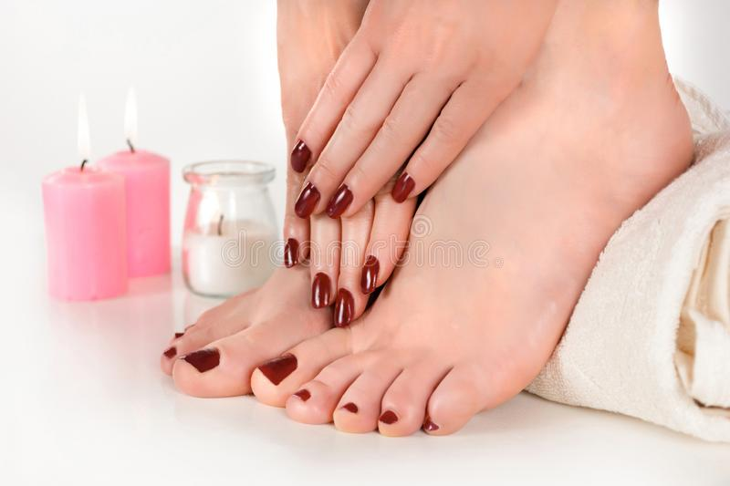 Female beautiful feet with burgundy color pedicure and hands with manicure on towel. And candle in the background in beauty studio. Manicure and pedicure royalty free stock photo