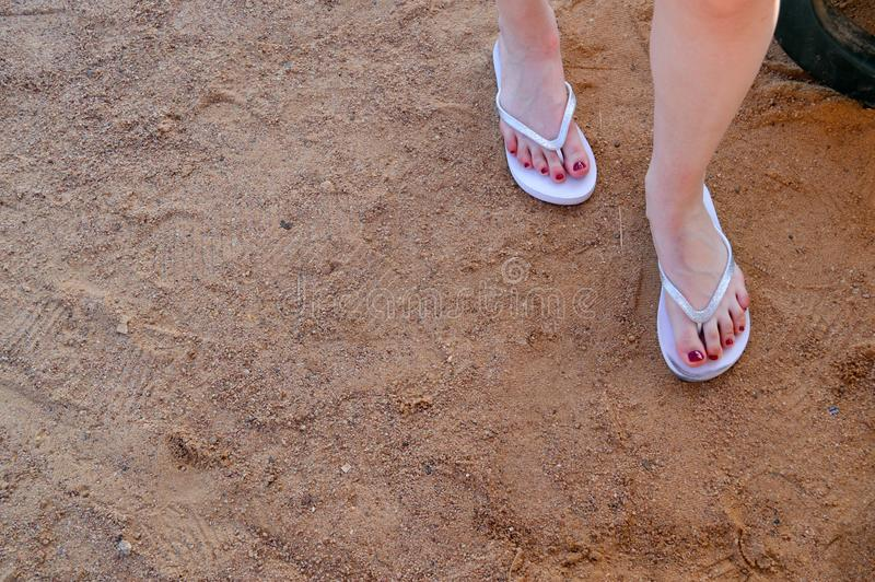 Female beautiful tender legs in white flip flops with a red pedicure on a background of yellow sand and a place for a copy space. The background stock photo