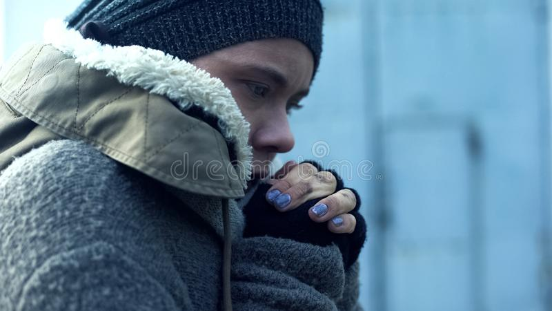 Female beggar feeling cold outdoors, homelessness problem, poverty despair. Stock photo stock images