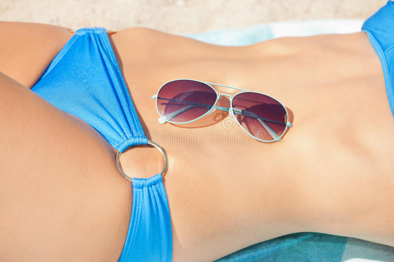 Female belly, bikini and shades royalty free stock photography