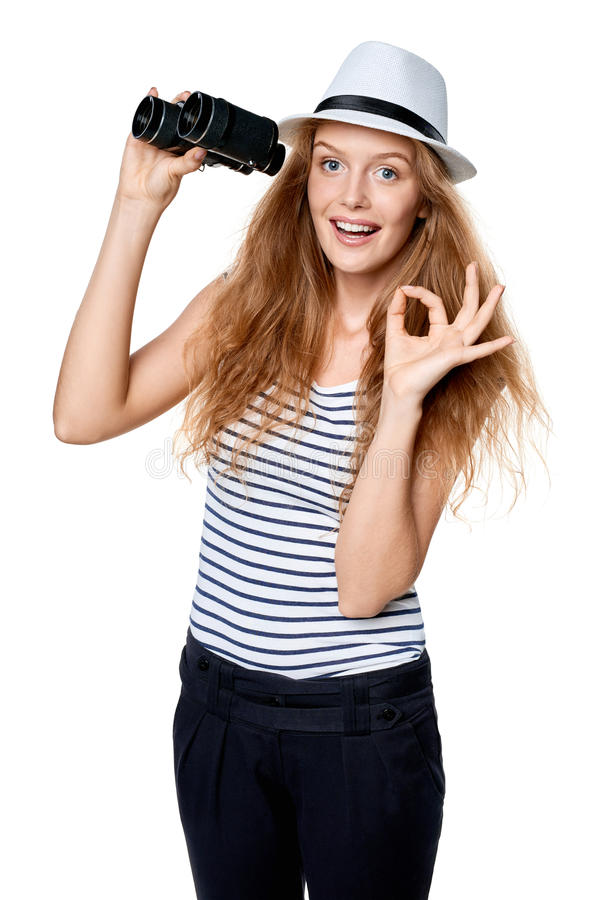 Female with binoculars gesturing OK. Happy emotional young beautiful teen female in striped tee and white straw fedora hat holding binoculars and looking at royalty free stock photo