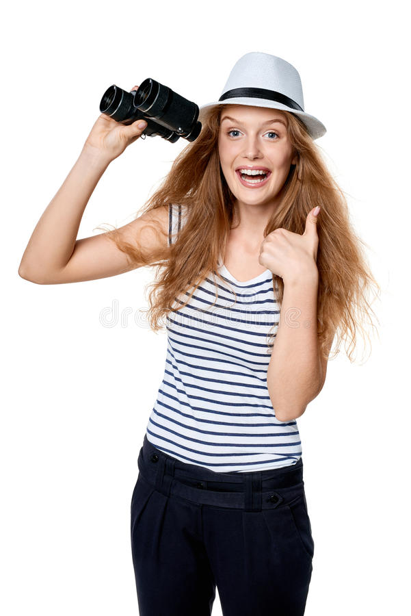 Female with binoculars gesturing thumb up. Happy emotional young beautiful teen female in striped tee and white straw fedora hat holding binoculars and looking stock photos