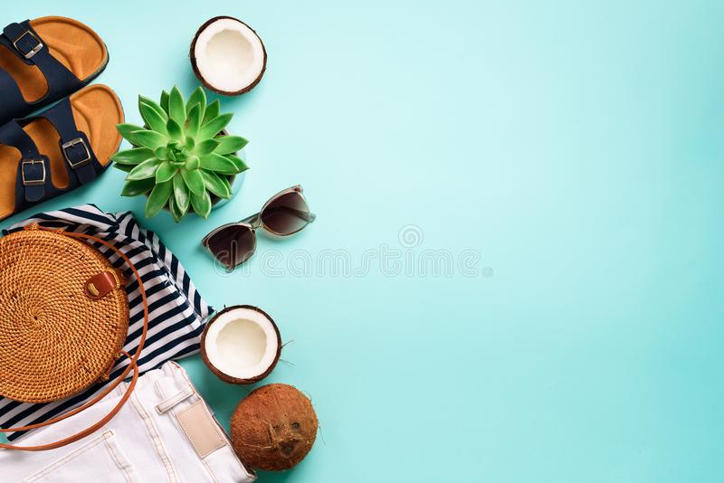 Female birkenstock sandals, jeans, striped t-shirt, rattan bag, coconut and sunglasses on blue background with copy stock image