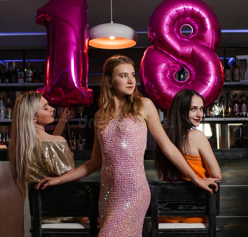 Female 18 birthday party in night club. Young women company in bar, stylish friends. Beautiful models, celebration together, beauty concept royalty free stock image