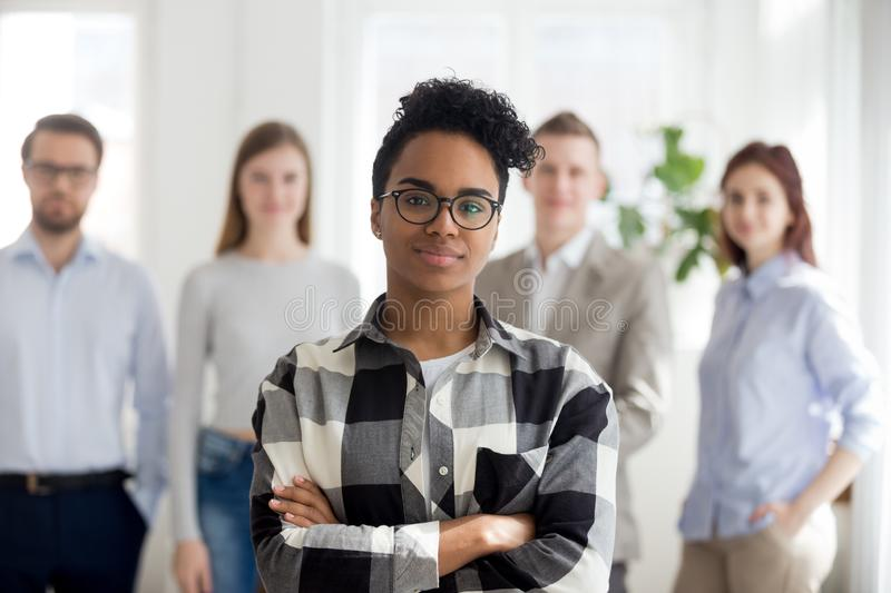 Female black millennial employee standing foreground arms crosse. Female African American millennial employee standing foreground with arms crossed, colleagues royalty free stock photography