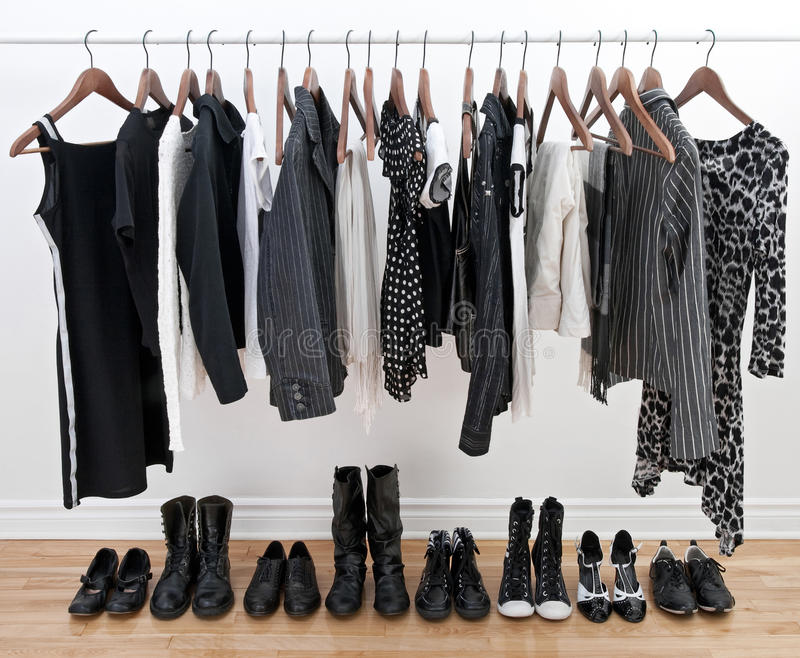 Female black and white clothes and shoes. Female black and white clothes on a pole and shoes on a wooden floor royalty free stock images