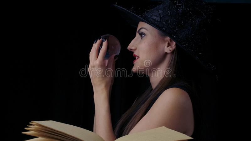 Female in a black witch costume and hat, holds in her hands a transparent magic ball over a book and conjures. close-up stock photography