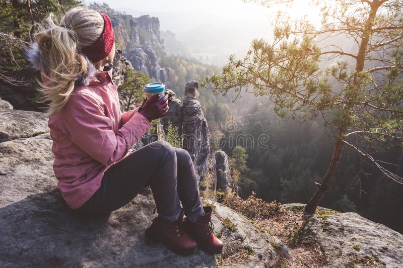 Female blond hiker outdoor clothing with coffee cup in hands on limestone rock enjoying sunset back lit view of mountain. Ridge and forest down the valley royalty free stock photo