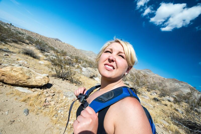 Female blonde hiker spots to squit to look off into the distance. As she hikes through the California desert in the Coachella Valley royalty free stock photography
