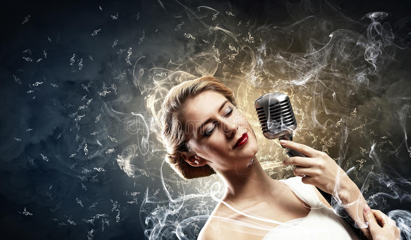 Female blonde singer. Image of female blonde singer holding microphone against smoke background with closed eyes royalty free stock photos