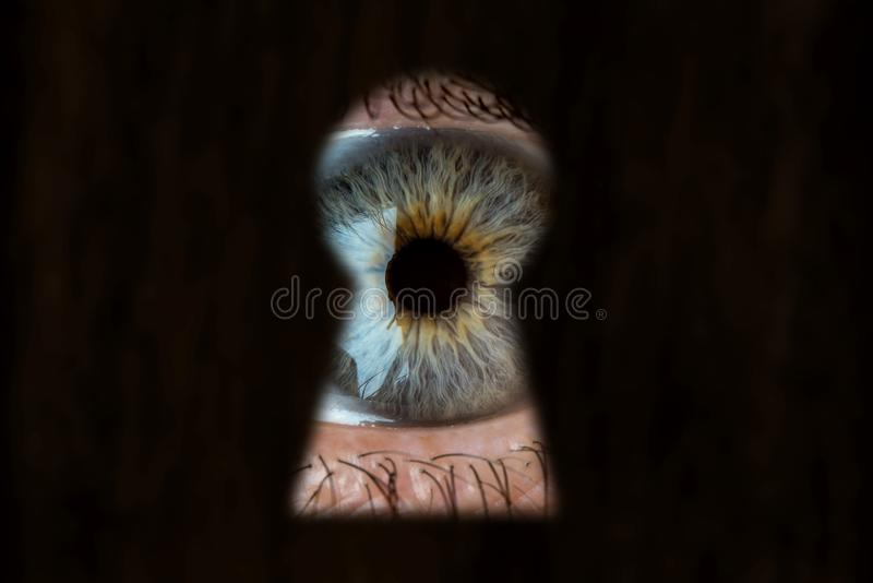 Female blue eye looking through the keyhole. Concept of voyeurism, curiosity, Stalker, surveillance and security. Female blue eye looking through the keyhole royalty free stock images