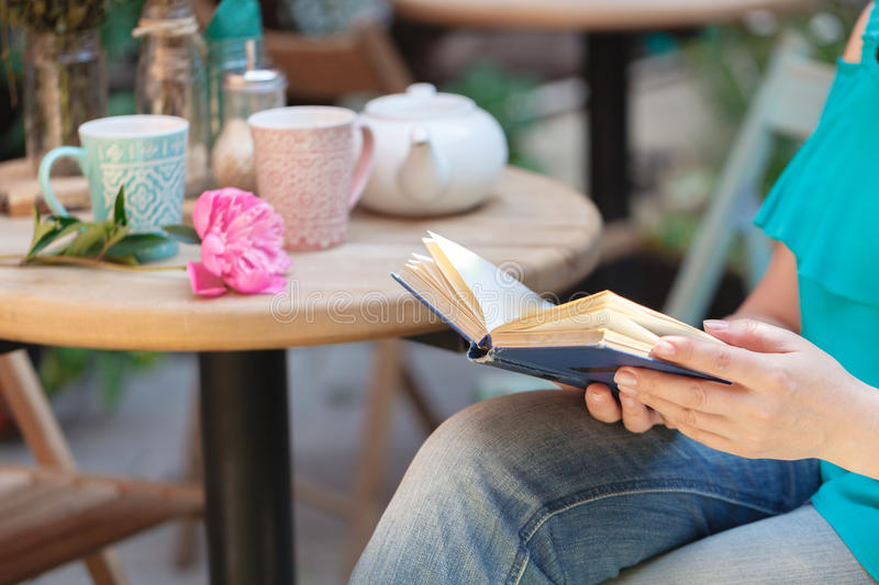 Female with a book outdoors cafe royalty free stock image