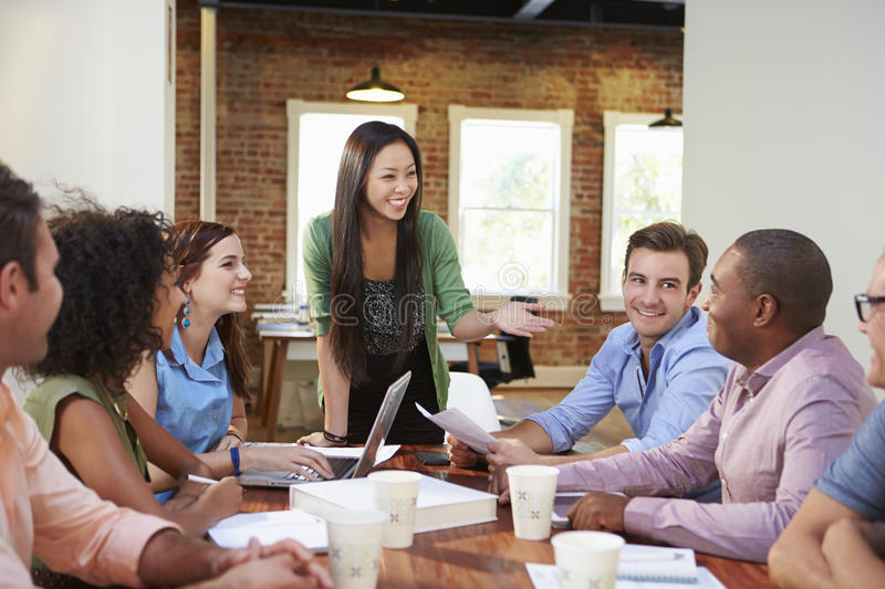 Female Boss Addressing Office Workers At Meeting stock photos