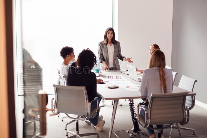 Female Boss Gives Presentation To Team Of Young Businesswomen Meeting Around Table In Modern Office royalty free stock photos